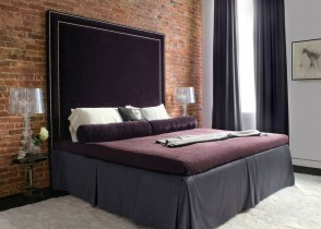 Purple upholstered bed with nails brick wall